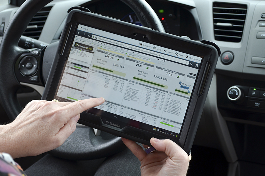 This image shows a tablet with DemandLink on it taken over the shoulder of the driver's side of a car