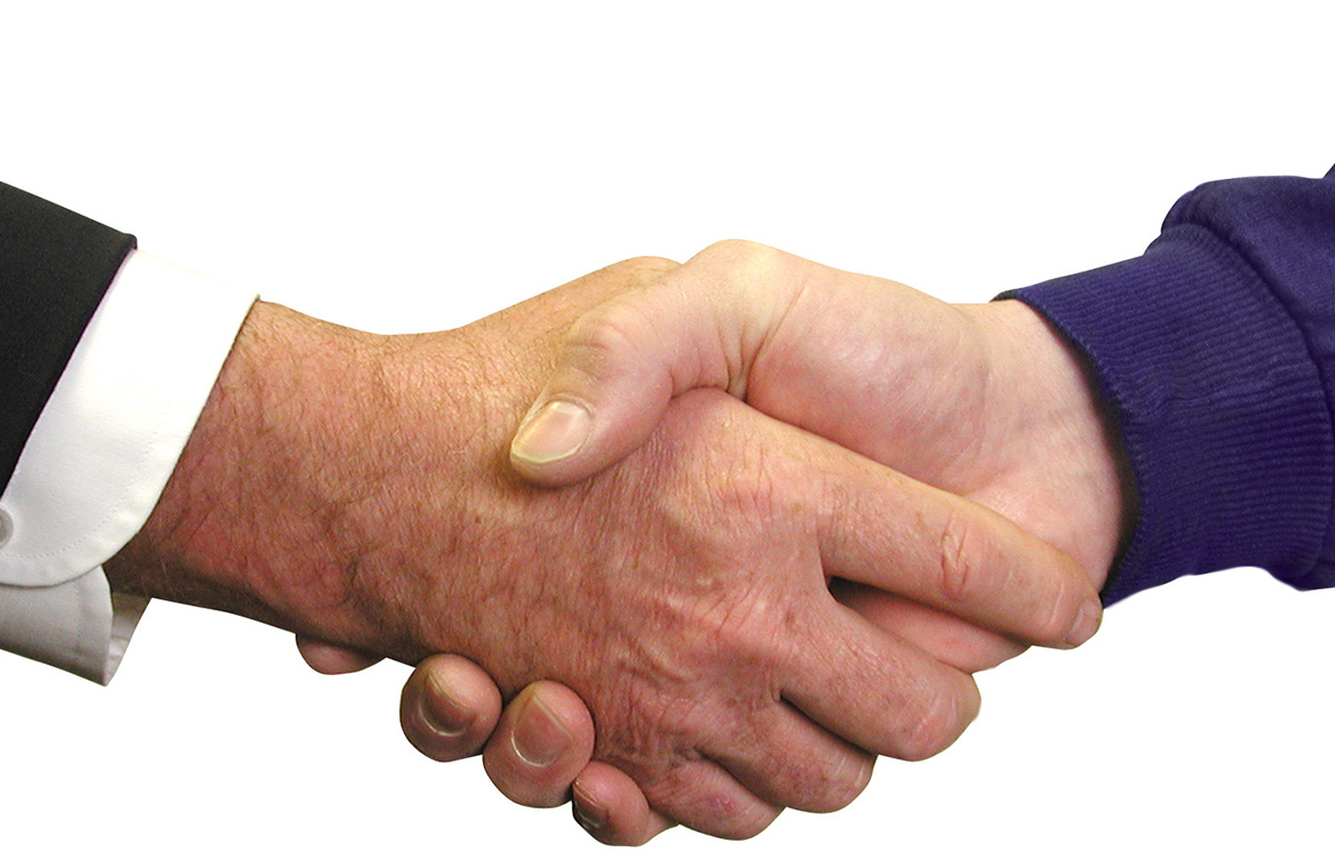 This is a close-up image of two men shaking hands.